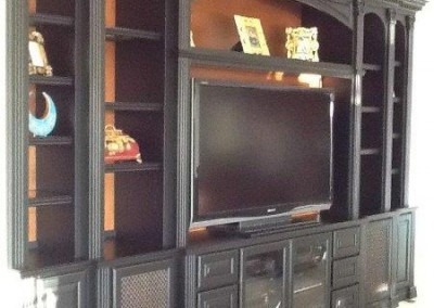 Entertainment center with open backing that shows painted wall